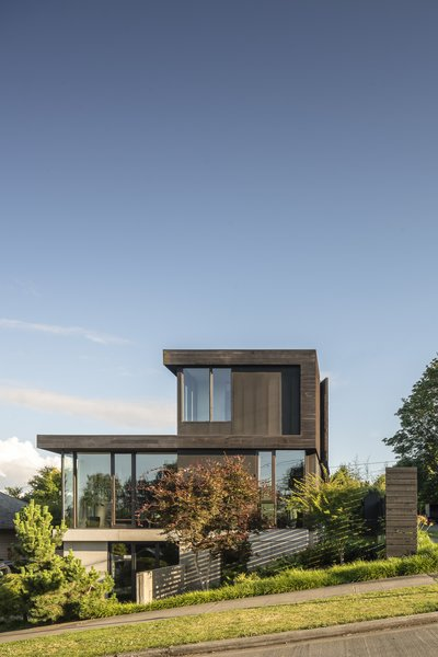 The Helen Street Residence by mwworks is set on a corner lot northeast of downtown Seattle. The home's glass-enclosed main level is topped by a wood-clad roof plane and second-floor volume.