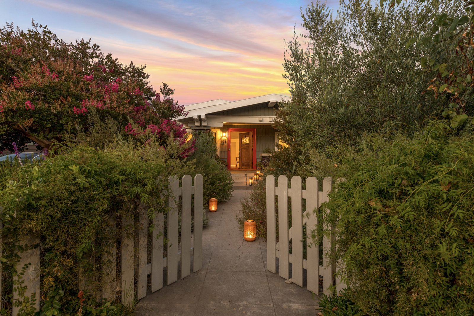 An inviting fence and walkway lead from the sidewalk to the lushly landscaped property.  Photo 16 of 16 in An Artfully Reimagined California Craftsman Asks $1.2M