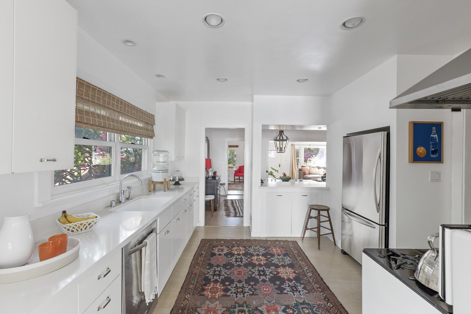 An updated kitchen occupies a rear corner of the home and is connected to the dining room by a small pass-through counter area. A row of cabinetry is flanked by a vintage Wedgewood range.  Photo 6 of 16 in An Artfully Reimagined California Craftsman Asks $1.2M