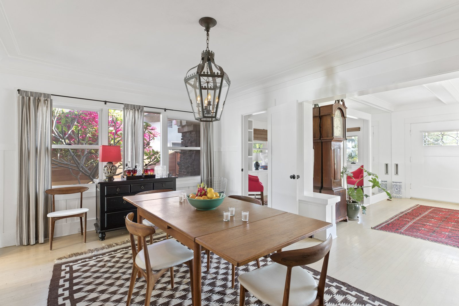 An open dining area sits between the living room and kitchen. Windows along one wall overlook bougainvillea trees along the side yard.  Photo 5 of 16 in An Artfully Reimagined California Craftsman Asks $1.2M