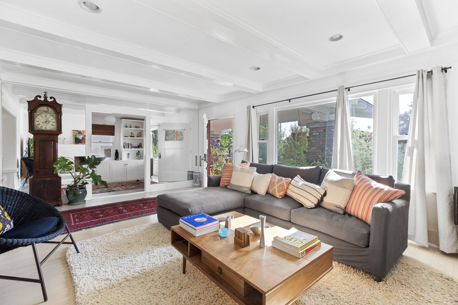 The living area basks in natural light thanks to a large picture window along one wall. The neutral, all-white color palette was recently refreshed in preparation for the sale.   Photo 3 of 16 in An Artfully Reimagined California Craftsman Asks $1.2M