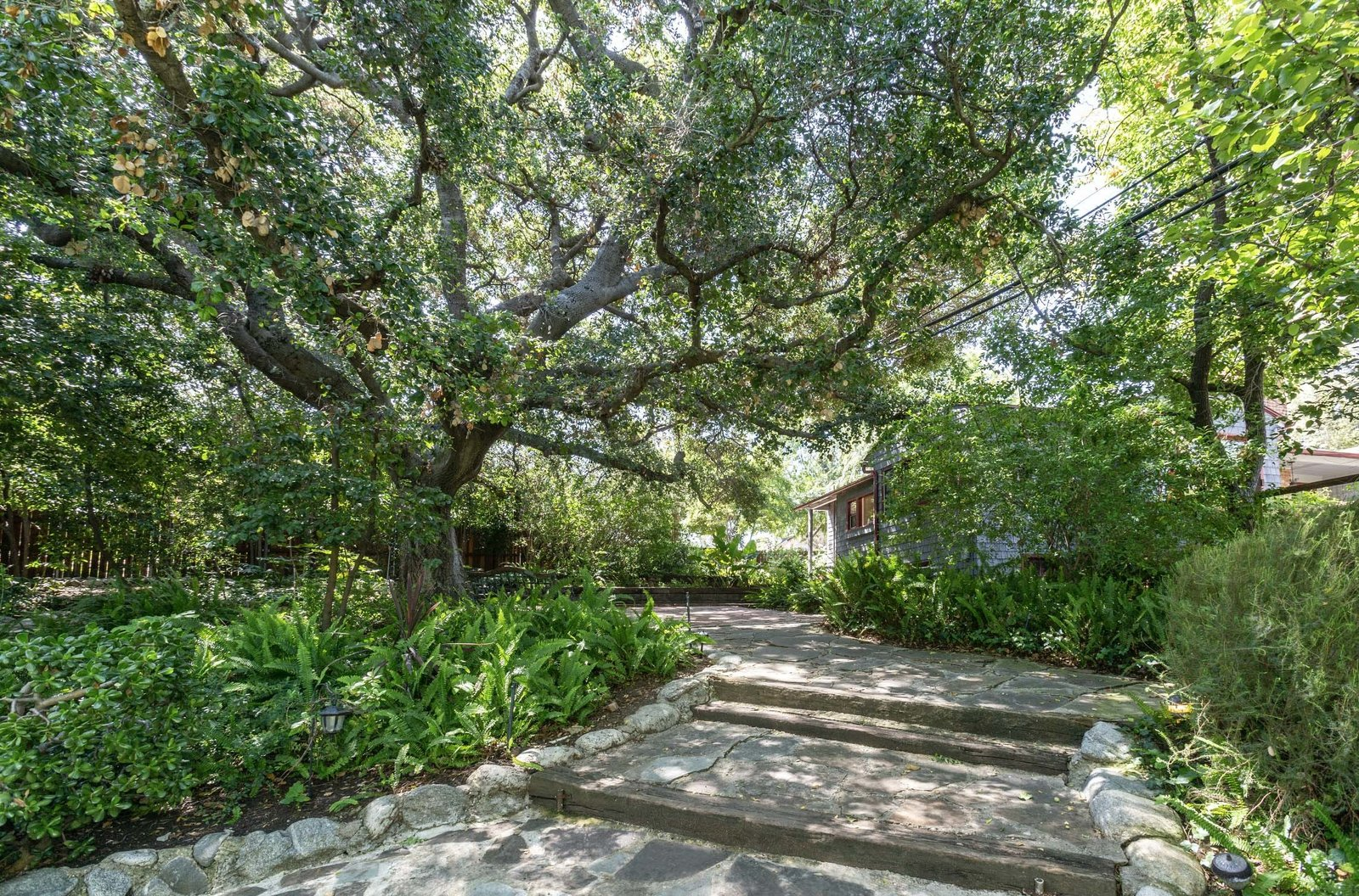 Numerous patios and pathways connect the compound.  Photo 12 of 22 in A Lush Los Angeles Compound With a Shingle-Clad Cottage and Lime-Green Home Seeks $2M