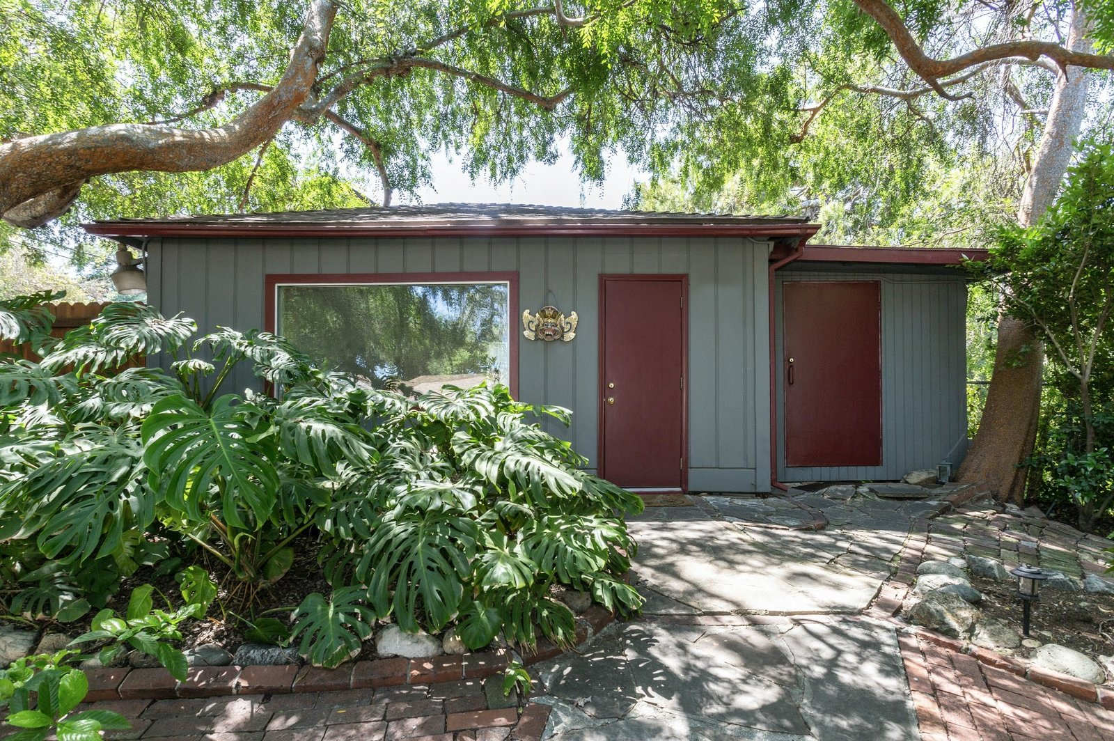 A studio and storage building also sits to one side of the property, offering a quiet spot for a home office or potential guest suite.  Photo 13 of 22 in A Lush Los Angeles Compound With a Shingle-Clad Cottage and Lime-Green Home Seeks $2M