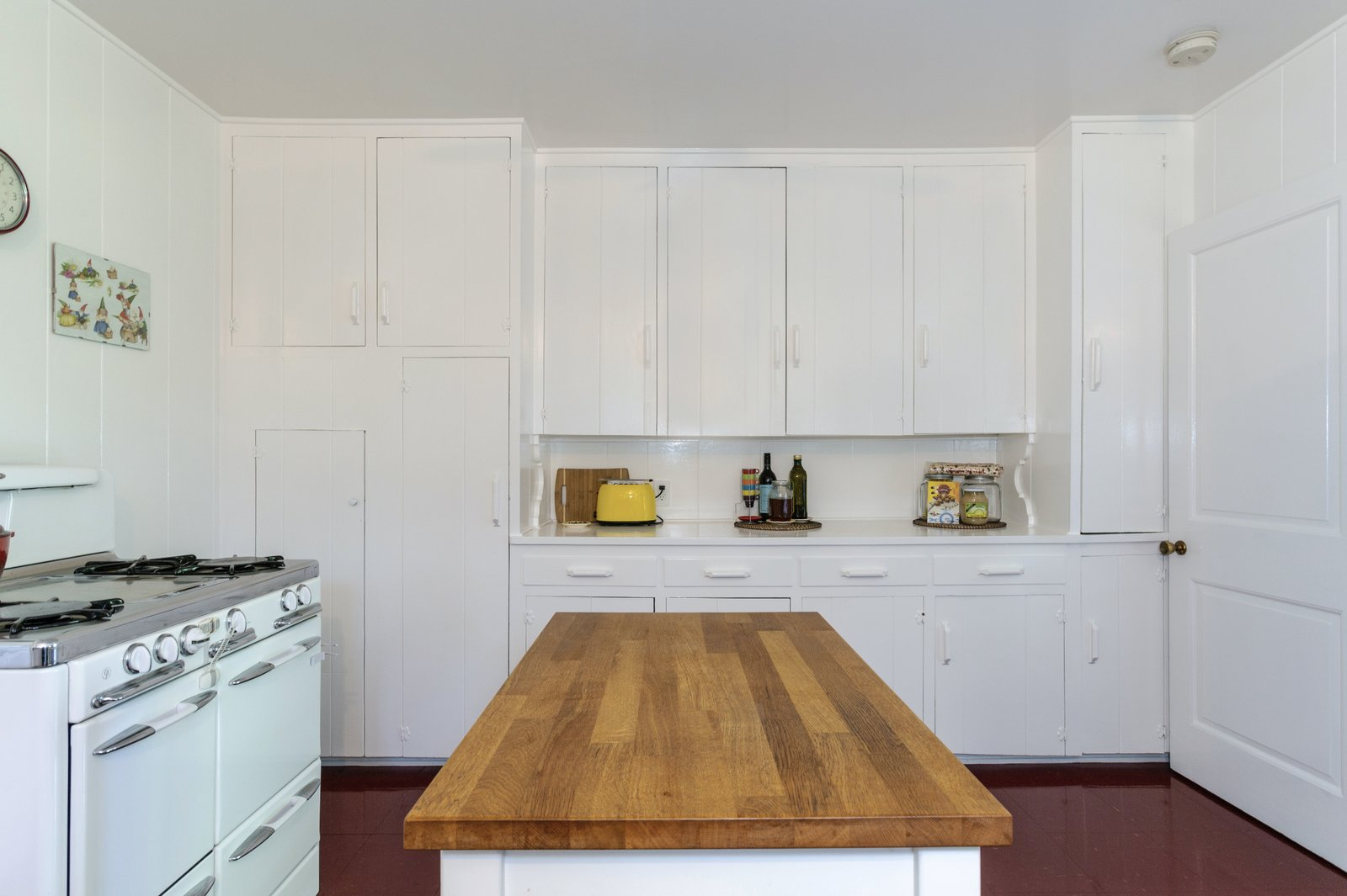 Another view of the kitchen shows cabinetry that lines the rear wall.  Photo 6 of 22 in A Lush Los Angeles Compound With a Shingle-Clad Cottage and Lime-Green Home Seeks $2M