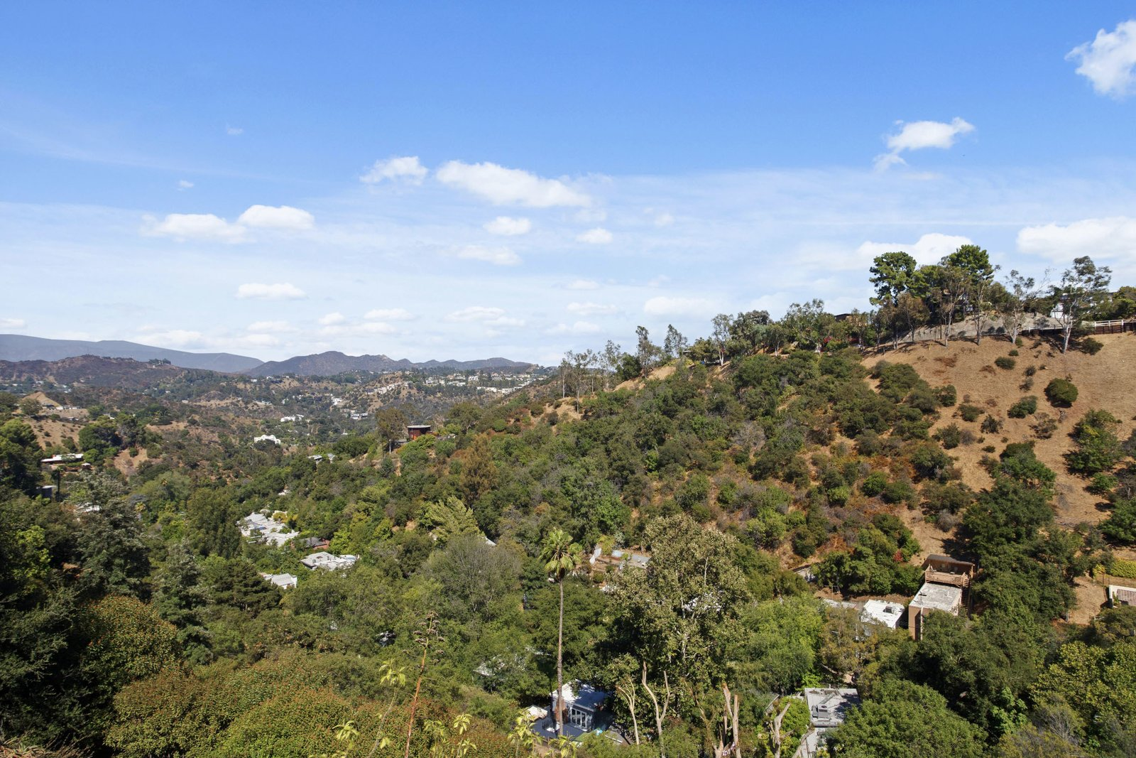 The outdoor space looks out to views of the surrounding hills and the San Gabriel Mountains further beyond.  Photo 17 of 17 in A Refined Midcentury Home on a Los Angeles Hilltop Lists for $2M