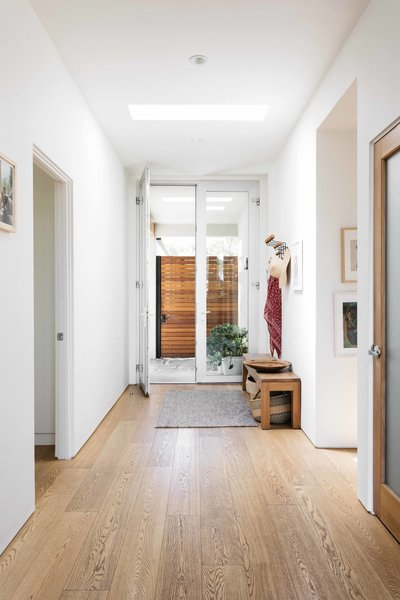 The sunlit entryway opens from an enclosed courtyard that separates the home from the street. French doors and an overhead skylight provide natural light.