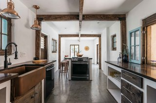 An updated kitchen fills one wing, offering stucco-and-wood cabinetry topped by mahogany butcher-block counters. Other features such as the copper sink and fixtures complement original post and beams.