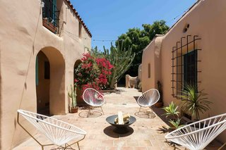 The paved courtyard is nearly 1,000 square feet, complete with archways and an adobe brick wall that encloses the rear of the space.