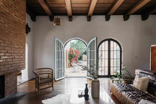 A pair of arched glass doors open to the courtyard, which fills the outdoor space between two wings of the home.