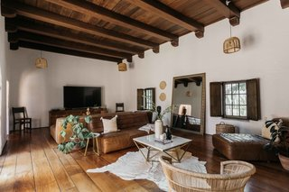 A large living area sits in the center of the home and looks out onto the courtyard. Features of the space include an original timber-beamed ceiling and hardwood floors.