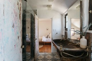 The bathroom features a tiled floor and shower, as well as a custom-made sink and vanity.