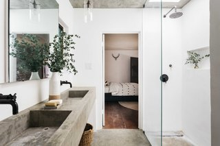 Concrete sinks and flooring complete the modern bath, which is also illuminated by a skylight above the shower.