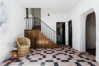 Inside, pale pink tiles line the entryway floor, contrasting with whitewashed plaster walls. The living room is located through an archway on the right, while the kitchen is straight ahead.