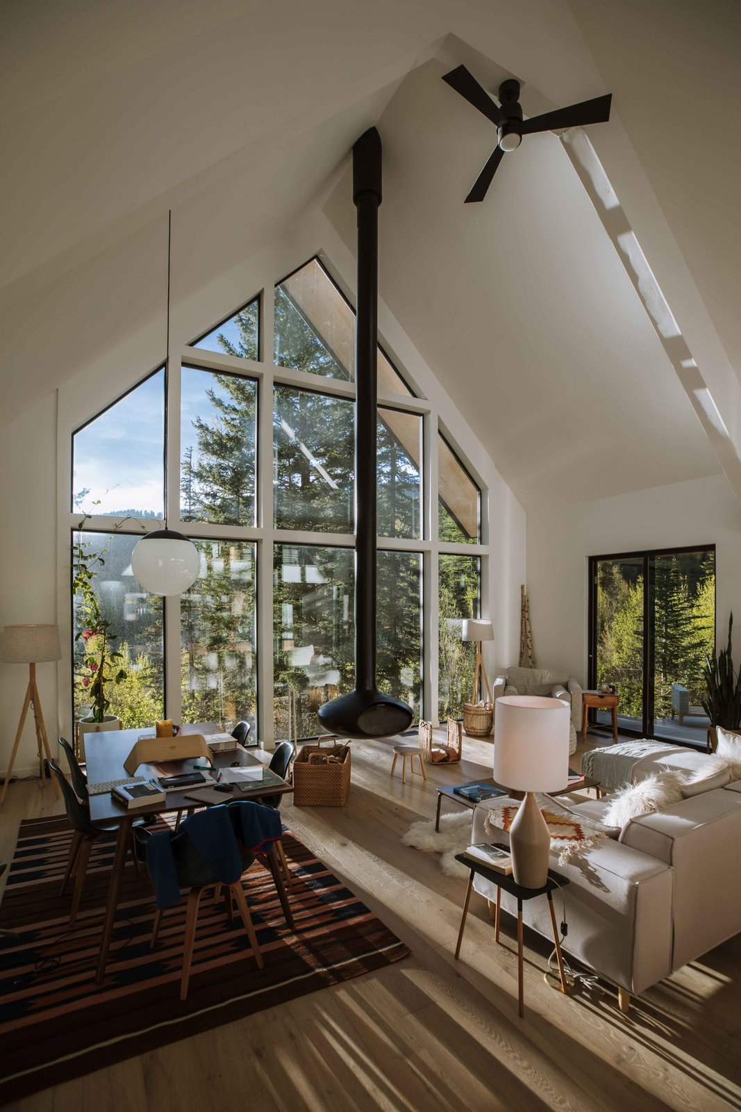 "Living, Chair, Sectional, Hanging, Lamps, Sofa, Pendant, Light Hardwood, Rug, and Wood Burning At Alex Strohl and Andrea Dabene's Nooq House in the Rocky Mountains of northwest Montana, highlights include a suspended fireplace, cathedral ceilings, and expansive windows. ""The windows are my favorite feature. I've loved seeing the colors change in the fall, snow in the winter, and bears in the spring,"" says Andrea.  Living Sectional Lamps Photos from A Pair of Adventurous Photographers Open the Doors of Their Epic Mountain Hideaway"