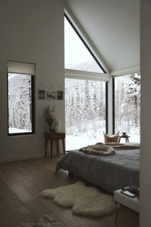 Floor-to-ceiling windows in one corner of the master bedroom frame views of a frozen landscape.