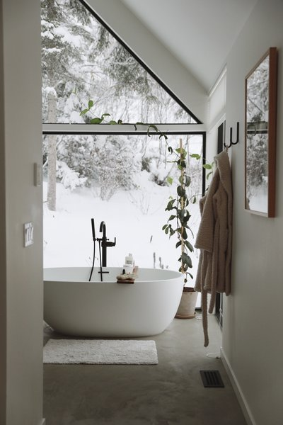 The master bathroom at the opposite end of the gabled section mirrors the window design. A soaking tub provides a spot to unwind.