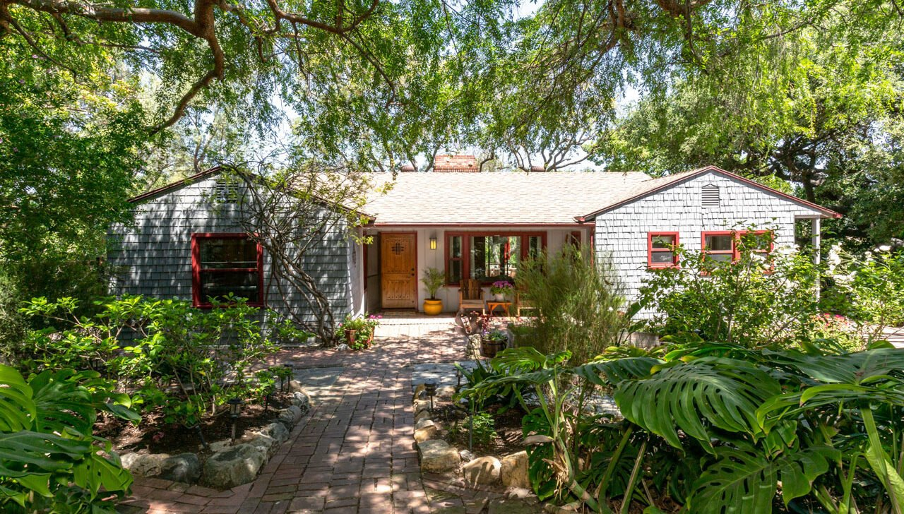 Taking up four lots, this secluded property also includes a detached studio and verdant green spaces.  Photo 1 of 22 in A Lush Los Angeles Compound With a Shingle-Clad Cottage and Lime-Green Home Seeks $2M