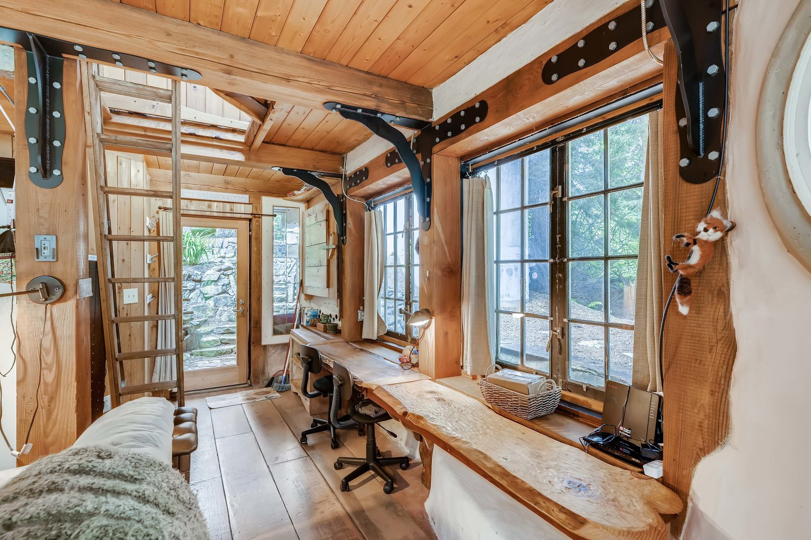 A built-in desk runs along one side of the space. Numerous windows bring sunlight in from all sides of the home.  Photo 7 of 15 in A Weird and Wonderful Cob Cottage in a Washington Co-Op Asks $500K