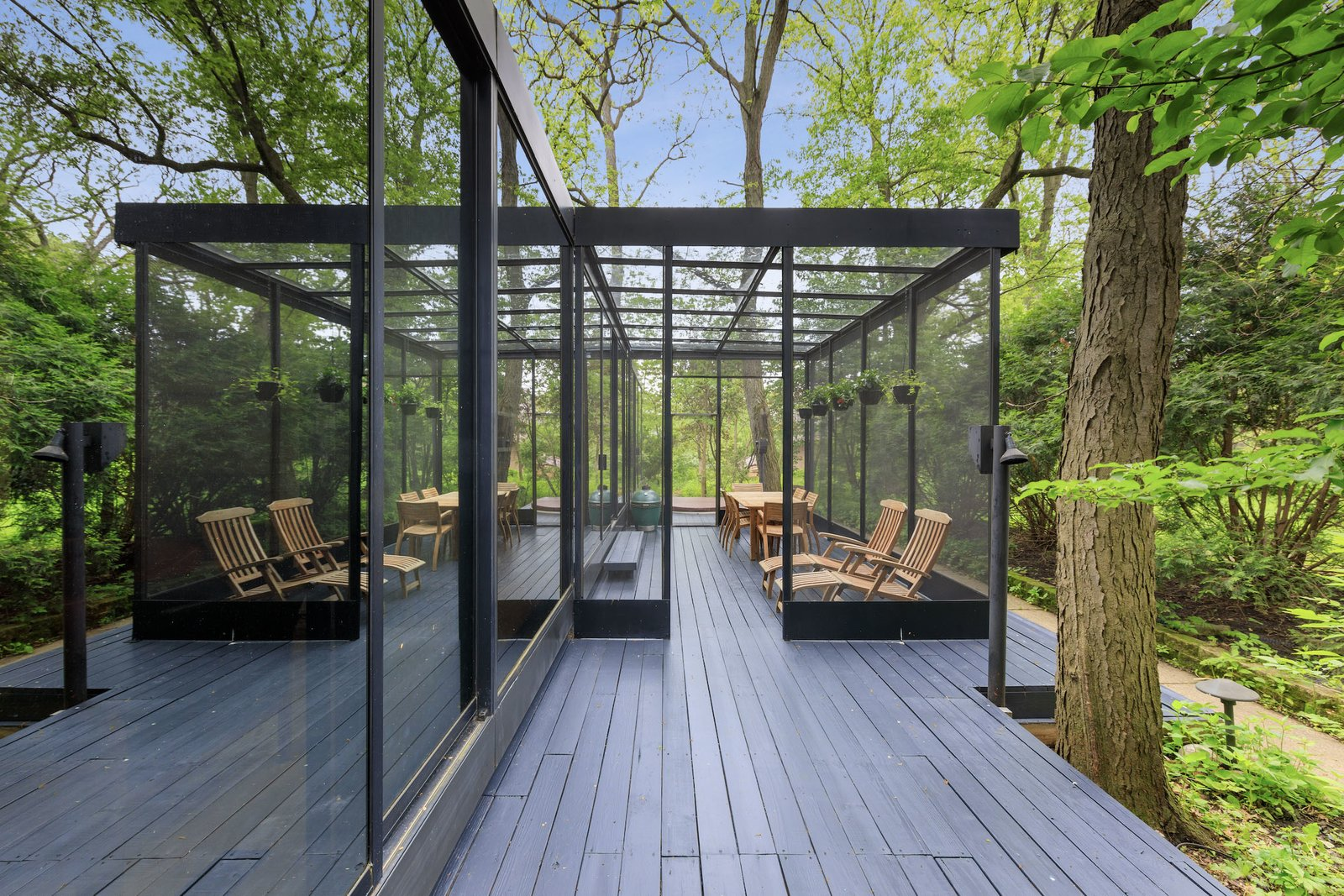 Another view of the exterior shows one of two decks that extends off of the home.  Photo 14 of 15 in A Blackened Steel and Glass House Outside of Chicago Hits the Market for $825K
