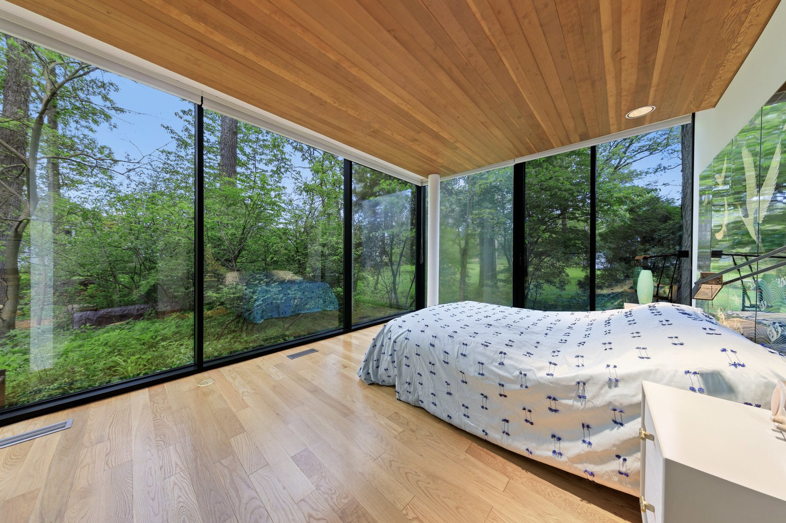 Back inside, the primary bedroom is located in a rear corner of the home. Sliding glass doors provide direct access to the outdoors along one side.  Photo 8 of 15 in A Blackened Steel and Glass House Outside of Chicago Hits the Market for $825K
