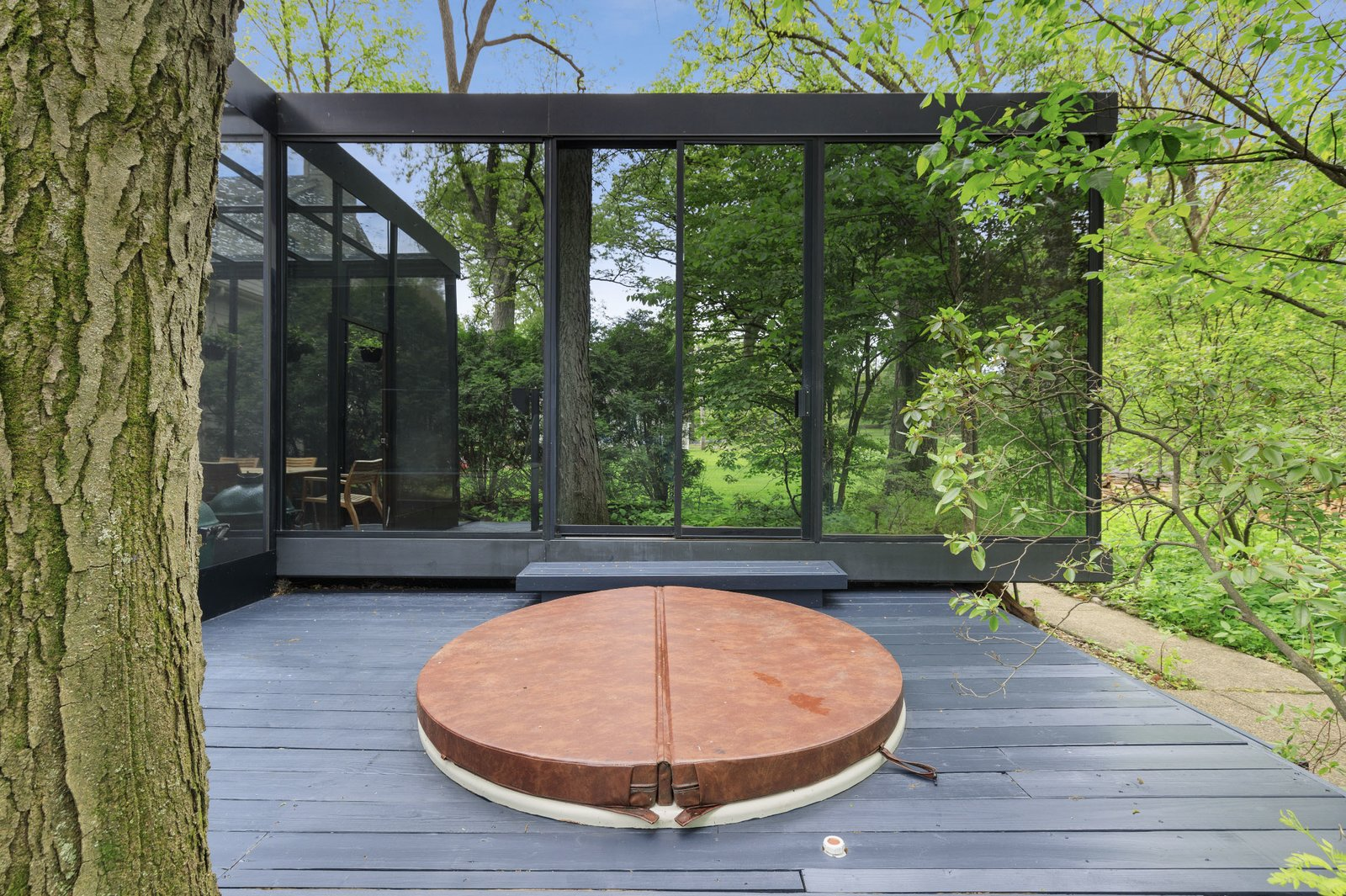 On the opposite side of the solarium, the second deck features a hot tub.  Photo 15 of 15 in A Blackened Steel and Glass House Outside of Chicago Hits the Market for $825K