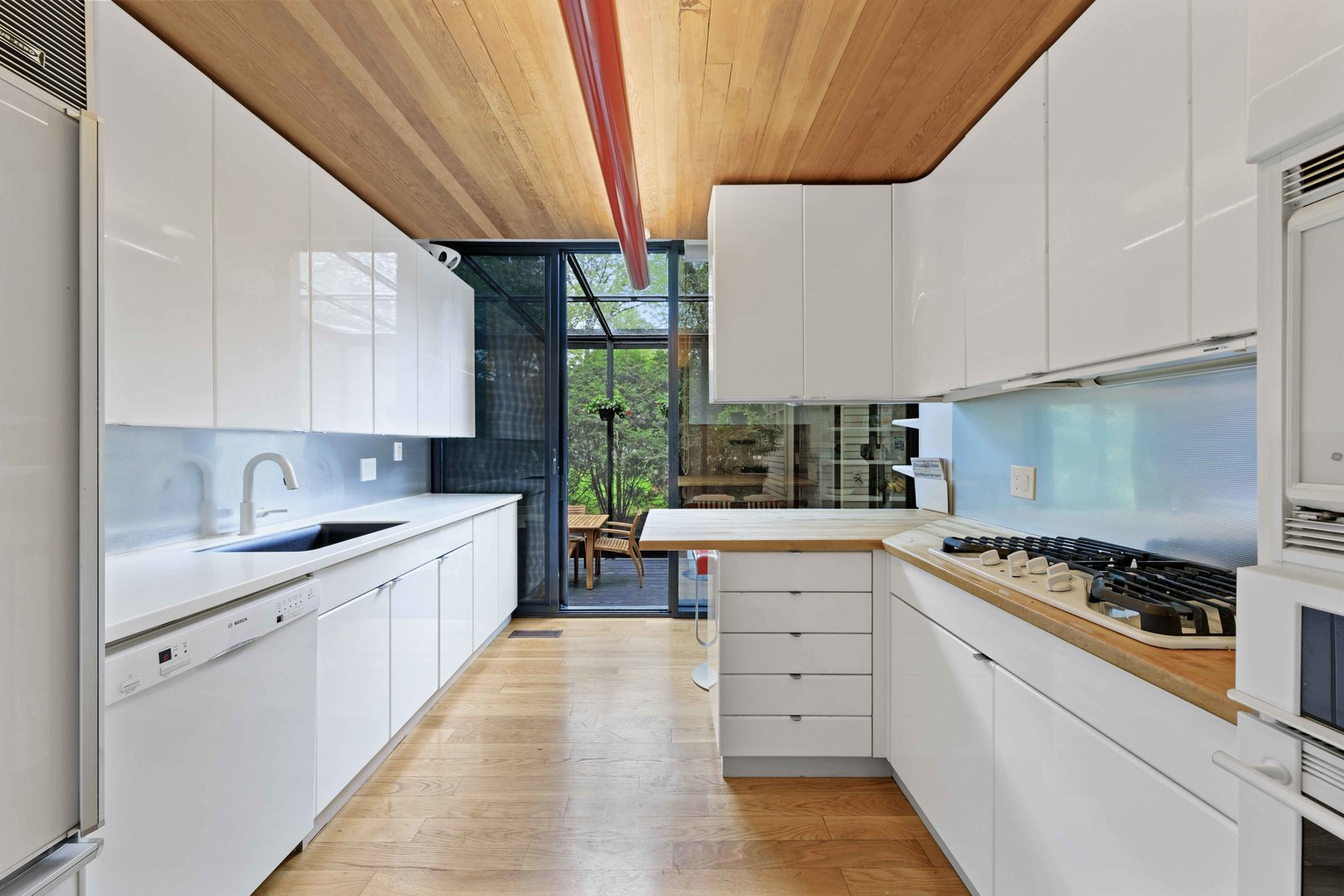 Another view of the kitchen shows the tube light fixture that runs the length of the space. At the opposite end, a sliding glass door opens to a solarium.  Photo 6 of 15 in A Blackened Steel and Glass House Outside of Chicago Hits the Market for $825K