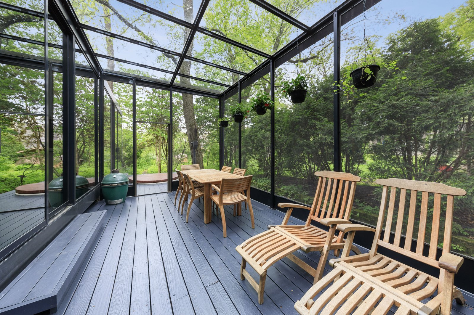 A closer look at the solarium. The glass-enclosed space opens to small decks at both ends.  Photo 7 of 15 in A Blackened Steel and Glass House Outside of Chicago Hits the Market for $825K