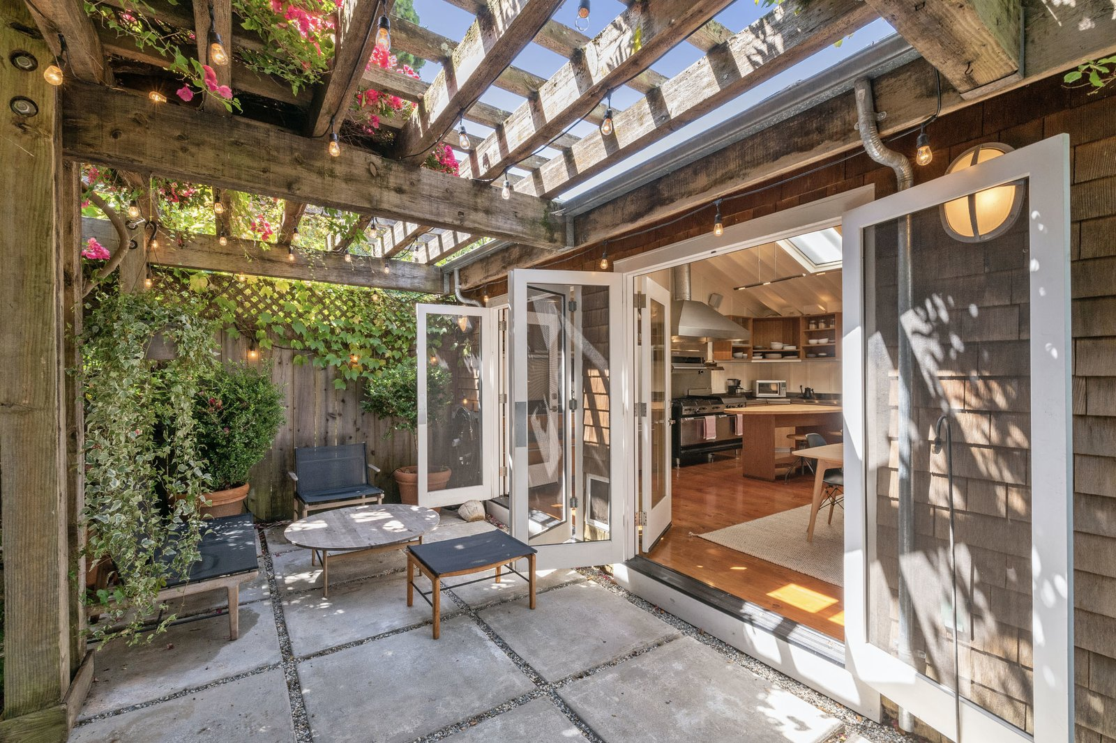 Outside, a pair of French doors connect the kitchen/dining area with a pergola-topped patio.  Photo 11 of 13 in An Idyllic Cottage With a Garden Studio Seeks $1.8M in San Francisco