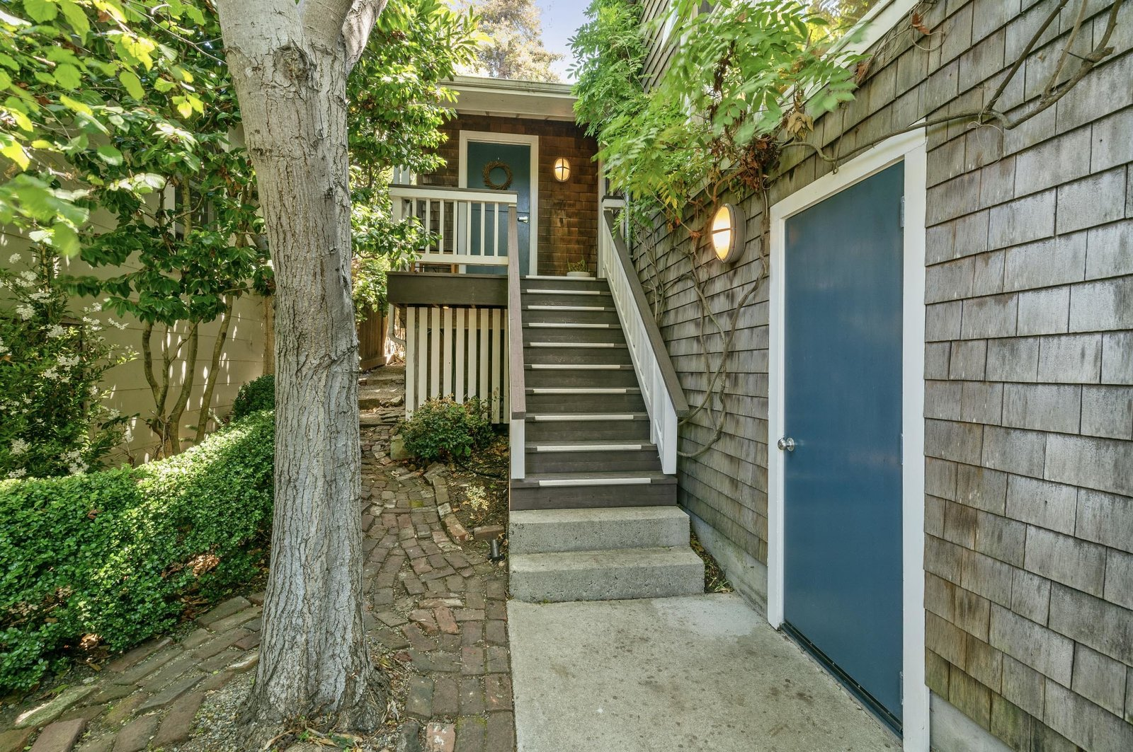 Along the front of the home, steps lead up to the front porch and a door provides access to the attached one-car garage. The property is located minutes away from some of Potrero Hill's most popular cafes and shops.  Photo 13 of 13 in An Idyllic Cottage With a Garden Studio Seeks $1.8M in San Francisco