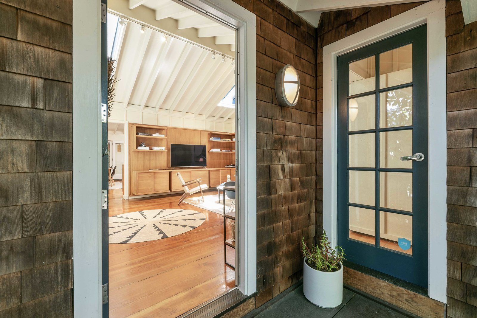 """A Dutch-style door opens from the front porch and leads directly into the sunlit living area. The wood-clad home is located along <span style=""""font-family: Theinhardt, -apple-system, BlinkMacSystemFont, &quot;Segoe UI&quot;, Roboto, Oxygen-Sans, Ubuntu, Cantarell, &quot;Helvetica Neue&quot;, sans-serif;"""">Arkansas Street and just around the block from Potrero Hill's popular 18th Street corridor of cafes and shops.</span>  Photo 1 of 13 in An Idyllic Cottage With a Garden Studio Seeks $1.8M in San Francisco"""