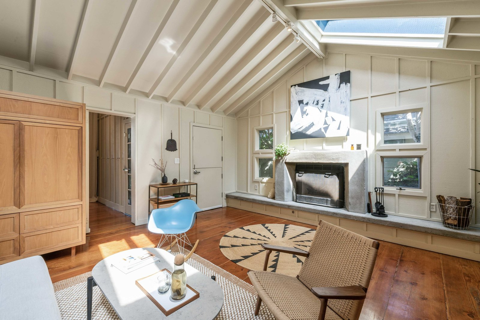 Another view of the living area shows a second skylight and the full-width fireplace hearth.  Photo 3 of 13 in An Idyllic Cottage With a Garden Studio Seeks $1.8M in San Francisco