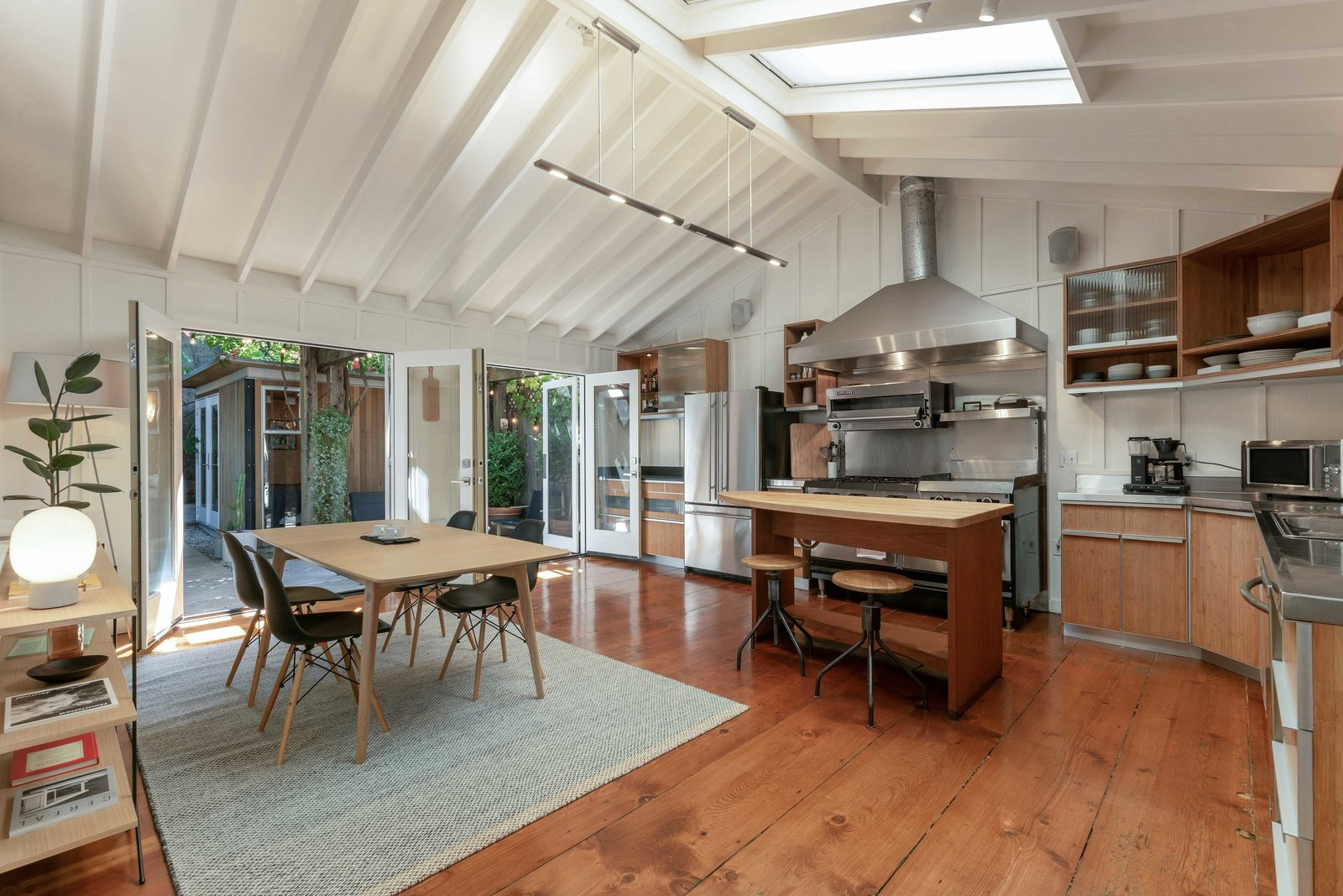 The living area flows into an open kitchen and dining area at the back of the home. A pair of French doors open to the shady backyard patio, while skylights provide additional sunlight.  Photo 4 of 13 in An Idyllic Cottage With a Garden Studio Seeks $1.8M in San Francisco