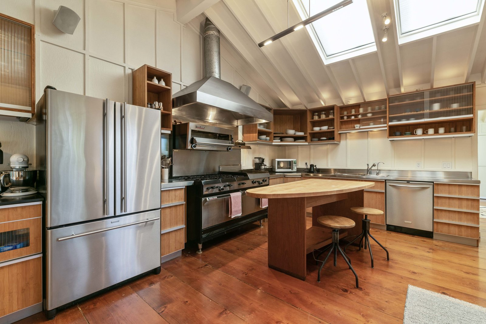 The commercial-grade kitchen features a Garland six-burner stove with built-in griddle, as well as a salamander broiler hanging overhead  Other features include custom bamboo cabinetry and stainless steel counter tops around the perimeter.  Photo 5 of 13 in An Idyllic Cottage With a Garden Studio Seeks $1.8M in San Francisco