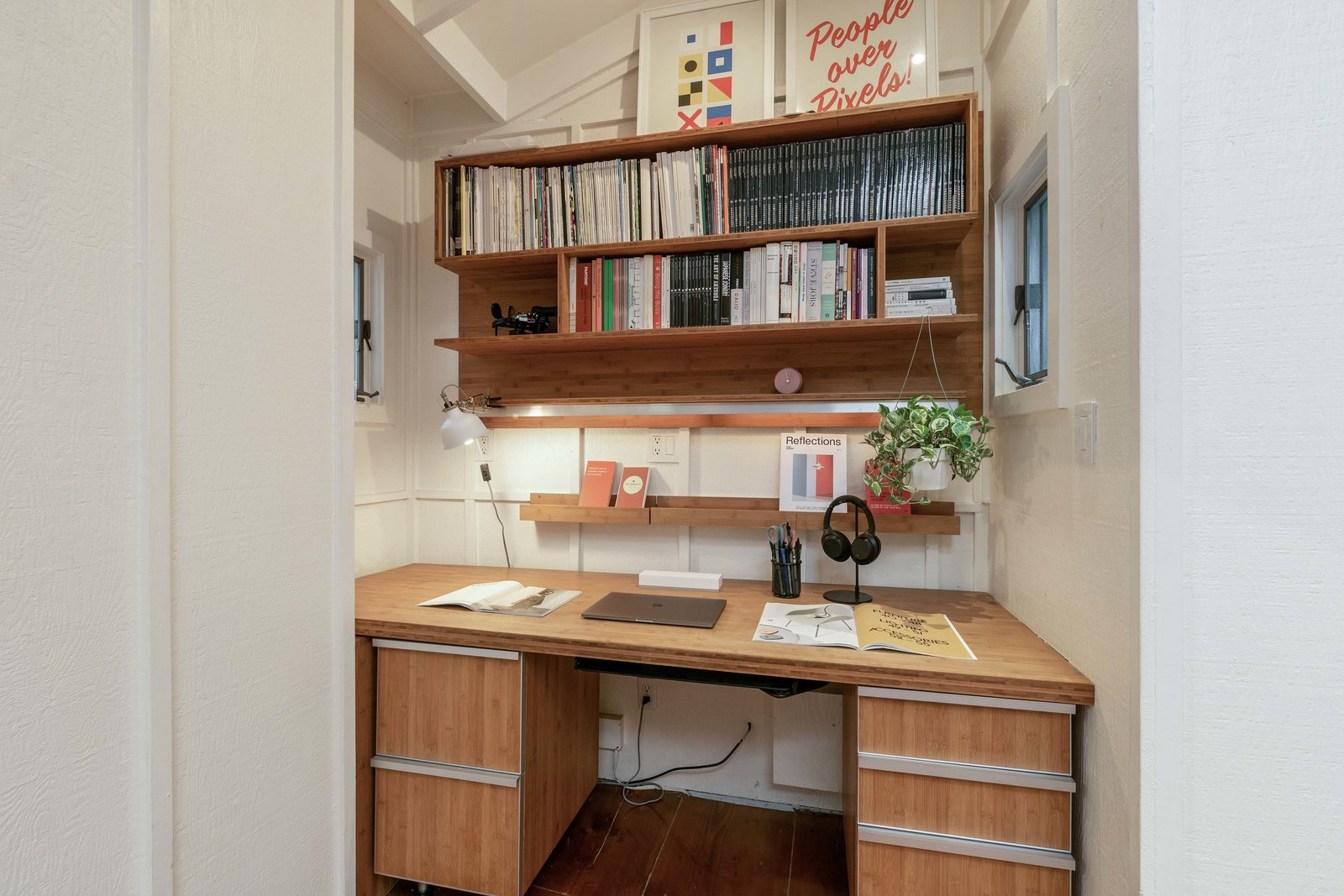 A built-in desk occupies a nook in one corner of the kitchen/dining area.  Photo 7 of 13 in An Idyllic Cottage With a Garden Studio Seeks $1.8M in San Francisco