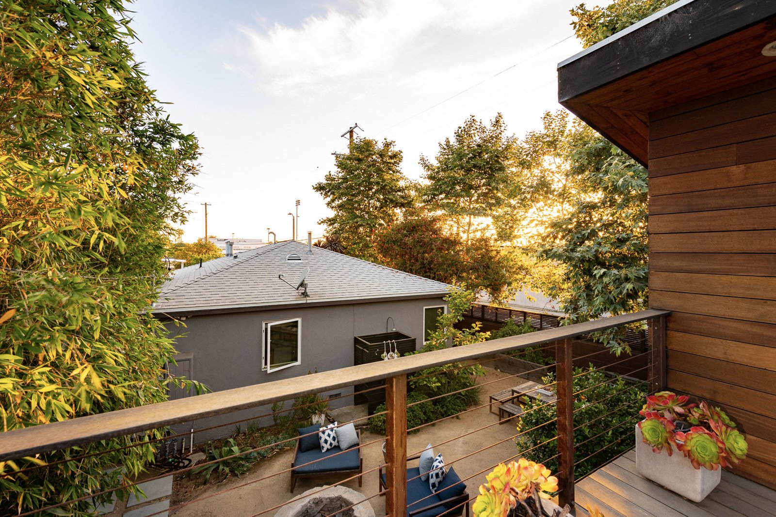 """A view from the studio balcony shows the front bungalow and central patio area. Creative director Matt Titone's architect brother Sam and interior designer wife Courtney <span style=""""font-family: Theinhardt, -apple-system, BlinkMacSystemFont, &quot;Segoe UI&quot;, Roboto, Oxygen-Sans, Ubuntu, Cantarell, &quot;Helvetica Neue&quot;, sans-serif;"""">Husk transformed the garage into an inviting guest/work space several years ago.</span>  Photo 1 of 17 in The """"Surf Shacks"""" Author Lists His Venice Bungalow and Backyard Guesthouse for $1.6M"""