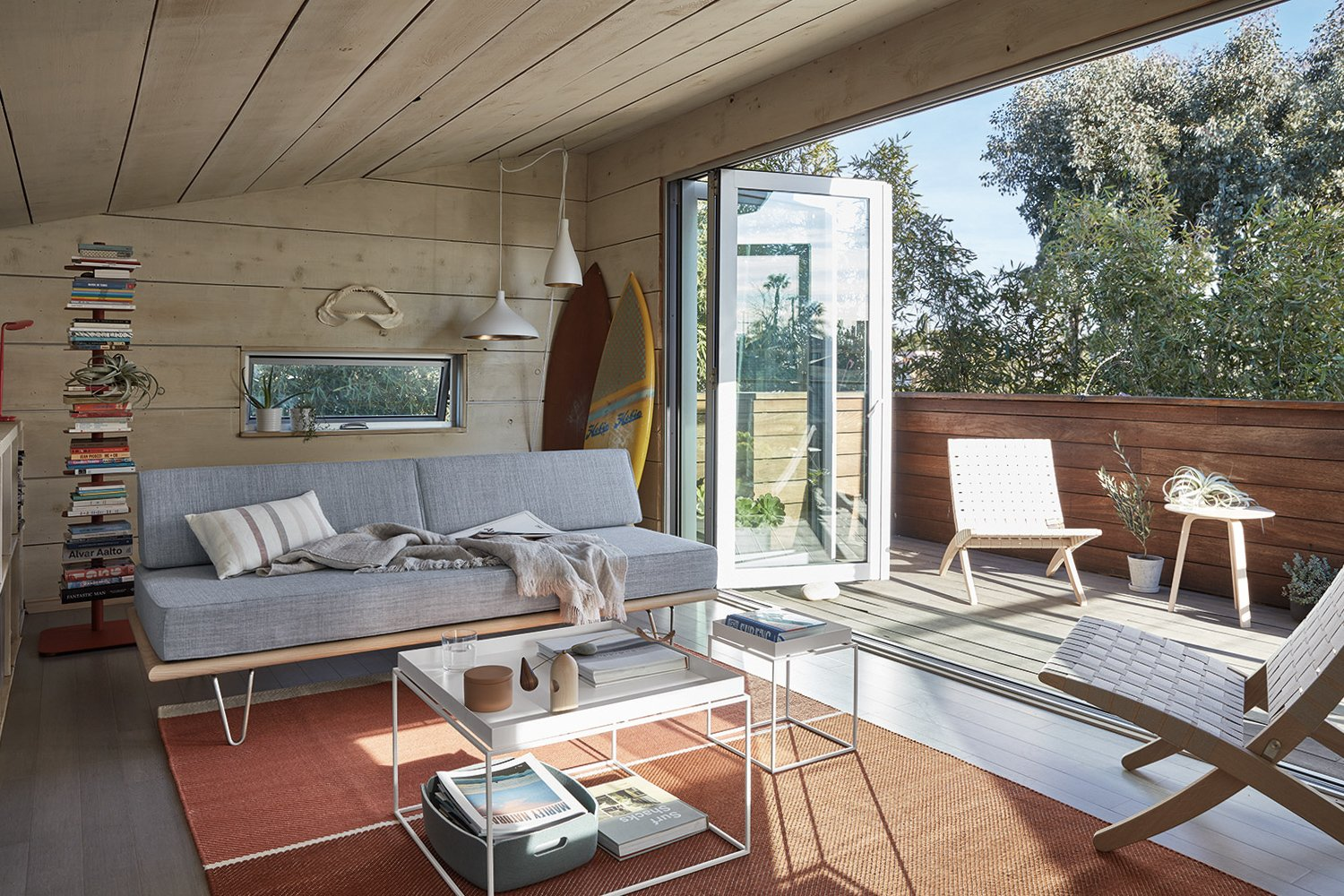"""Inside the studio, bi-folding doors connect the balcony to a loft area. W<span style=""""font-family: Theinhardt, -apple-system, BlinkMacSystemFont, &quot;Segoe UI&quot;, Roboto, Oxygen-Sans, Ubuntu, Cantarell, &quot;Helvetica Neue&quot;, sans-serif;"""">hite-washed cedar covers the walls and ceilings throughout the interior.</span>  Photo 2 of 17 in The """"Surf Shacks"""" Author Lists His Venice Bungalow and Backyard Guesthouse for $1.6M"""