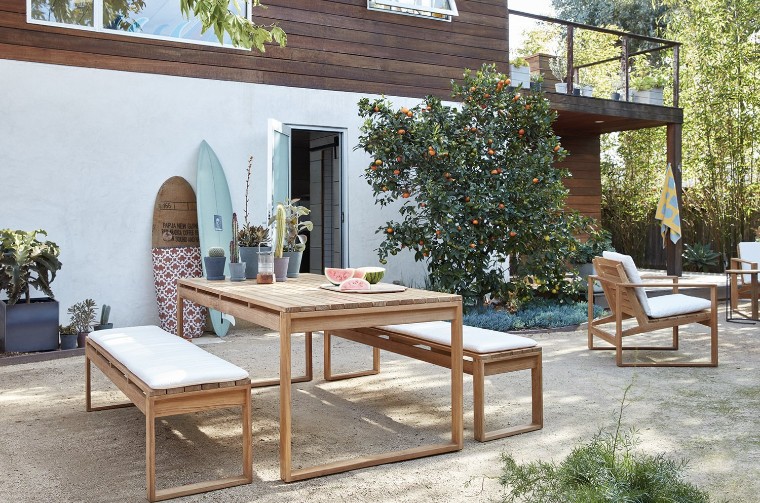 """The space between the studio and main house is now a large patio with several seating areas. A fence encloses the space and provides additional privacy along with lush plantings.  Photo 10 of 17 in The """"Surf Shacks"""" Author Lists His Venice Bungalow and Backyard Guesthouse for $1.6M"""