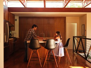 Homeowner John John Bhasme with his daughter. In addition to upgrading the HVAC and electrical systems, the renovation replaced the home's dated railings, extended the back wall of the kitchen, and installed walnut cabinetry and floors throughout. The Purist faucet is by Kohler, while the refrigerator is by GE and the Onyx recessed lights are by Nora Lighting.