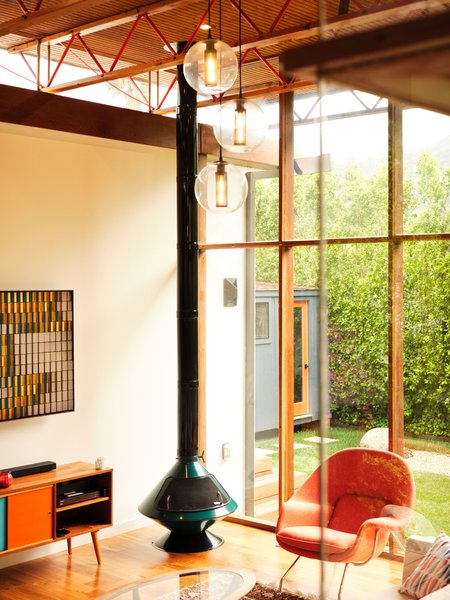 The designers removed extraneous elements added by others in the '70s so that Pedersen's striking exposed trusses could once again take center stage. They also relocated a vintage Aztec fireplace by Majestic from the den to the step-down family room and fitted it with chimney extensions from Malm Fireplaces. The Tribeca pendant lights by Sonneman, the vintage credenza from Sunset Bazaar, and the television by Samsung