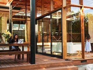 Sliding glass doors open to the partially covered deck, which is made of Cumaru decking by Advantage Lumber.