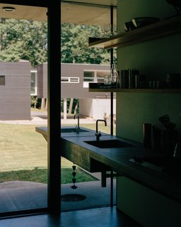 A custom sink by Vola in the kitchen has a twin on the outside for washing vegetables from the roof garden before bringing them indoors. The shelves are made of wood from trees felled on-site. The main house, visible in the background, was the designers' first residential commission.