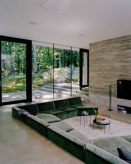 """The sunken living room is just one of many grade changes inside the structure. """"We were adamant that we didn't want something domestic,"""" says Andrew. """"We wanted something surprising, that was hyper-animated, and that, when you moved through it, changed all the time."""" The sofa, designed by the couple and Levenbetts, is upholstered in cotton velvet. The Habibi side tables are by Philipp Mainzer for e15, the fireplace tools by Fort Standard, and the doors by Fleetwood."""