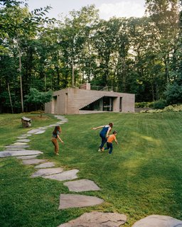 Niki Bergen and two of her children run up the hill by the guesthouse she and her partner, Andrew Zuckerman, built on their upstate New York property. The structure was designed by Levenbetts, the architecture firm also responsible for the older main house nearby.