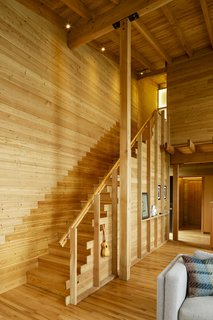 Contrasting wood finishes are visible throughout the house. The stair wall, for example, is smooth-sawn Douglas fir with a lacquer finish. Above touching height it transitions back to rough-sawn material.