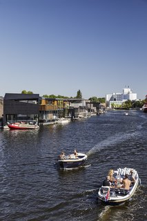 Residents of Schoonschip, a floating neighborhood in Amsterdam, designed their own houses, working with various architects and contractors. The water in the formerly industrial canal is now clean enough to swim in, but the opposite shore is still a landscape of warehouses.