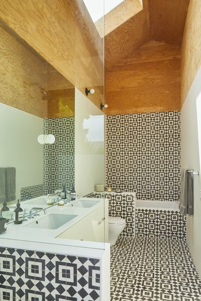 """Upstairs is a show-stopping oversize bathroom. """"When I chose the tile, I was afraid I was going to get sick of it,"""" says homeowner Melina Polly, """"but I do love it. It makes me happy every time I walk in there."""" The tiles are Fez by Granada Tile, the sinks are from Kohler, and the faucets are from Newport Brass."""