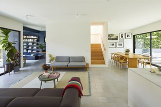 In the living area, a sofa from Hay faces a platform sofa from dk3, with a coffee table from Muuto in between. The floor tiles are from Concrete Collaborative and the wall paint is Atrium White by Benjamin Moore.