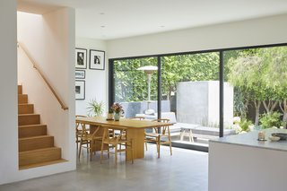 Inside the brightly colored home, walls of glass stretch along two sides of the lower level. The dining area features a Gather Dining Table by Jacob Plejdrup for dk3 and Wishbone dining chairs by Hans Wegner for Carl Hansen & Søn from Design Within Reach.
