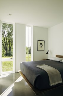 In the bedroom, an AJ table lamp by Arne Jacobsen for Louis Poulsen joins a Nelson Thin Edge Bed by George Nelson from Design Within Reach.