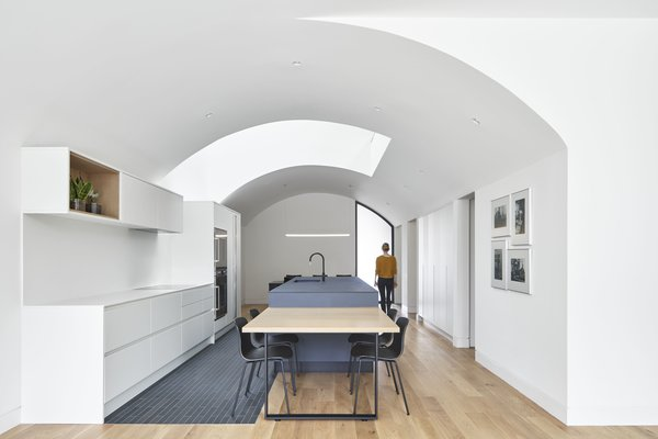 The kitchen is illuminated by the largest of several light wells. A dining table from Batay-Csorba flanks the end of an island, which also features a Disegno D4 faucet by Aquadesign and a XOOTUBE 38 IP40 pendant by LED Linear handing overhead. The space also features a Gaggenau cooktop along the opposite side.